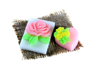 Handmade soap in the shape of a heart and rose on a napkin