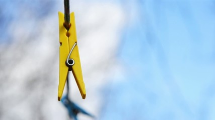 Yellow clothespin hanging on a rope and reeling from the wind