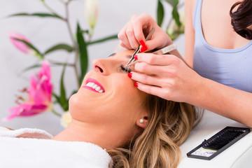 Frau erhält künstliche Wimpern bei Kosmetik