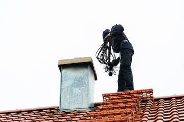 Kaminkehrer kehrt Schornstein auf Haus