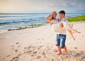 happy honeymooners couple at the beach