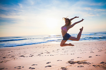 young girl dancing at the beach at blue sky background