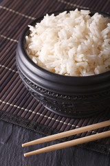 boiled rice in a black bowl close-up and chopsticks. vertical