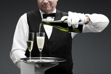 butler pouring champagne in glass