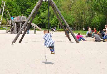 Fröhlicher Junge beim Spielen auf einem Spielplatz