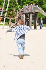 Fröhlicher Junge auf einem Spielplatz