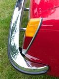 Rücklicht und Chromstoßstange eines roten Sportwagen