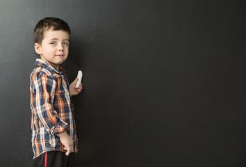 Cute little boy drawing on the chalkboard