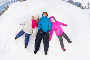Three kids lay on the snow with legs apart