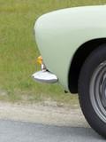 Lindgrüner Sportwagen der Fünfzigerjahre am Straßenrand in Lage