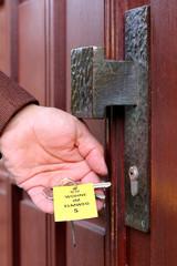 Demenzranker steckt Schlüssel in Tür, Schild