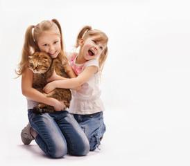 две девочки обнимают кошку и смеются