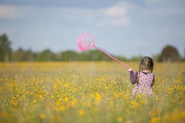 Girl with Butterfly Net in Field of Yellow Flowers