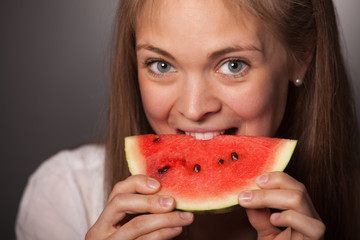 Attractive Girl Biting a Watermelon Against Gray