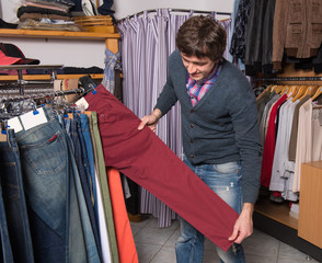 Handsome man choosing jeans during shopping