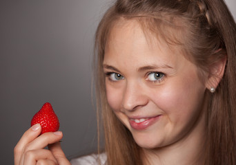 Smiling Girl Holding Red Strawberry Against Gray