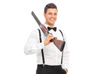 Elegant guy holding a shotgun over his shoulder isolated on whit