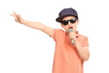 Little boy in hip hop outfit rapping on a microphone and gesturi