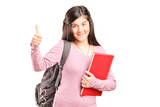Teenage schoolgirl giving a thumb up isolated on white