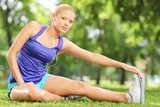Young female athlete stretching her leg seated on grass in a par