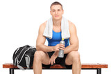 Young muscular athlete sitting on a wooden bench with a sports b