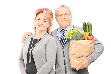 Mature couple posing with a bag of groceries