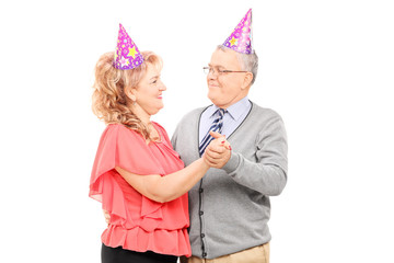 Mature couple with party hats dancing isolated on white