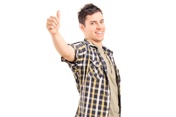 Relaxed young guy giving a thumb up isolated on white