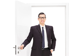 Young businessman in a black suit posing in front of an opened d