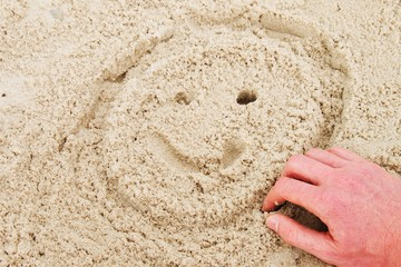 Hand is painting smiley face in summer beach sand