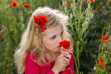 blond girl smelling poppy flowers