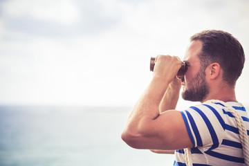 Sailor man looking through the binoculars