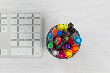 Pens and markers in container on top of desk