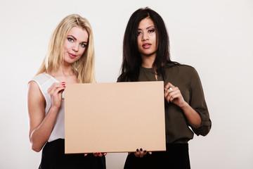 two women holding blank board