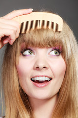 Closeup woman combing her fringe with comb