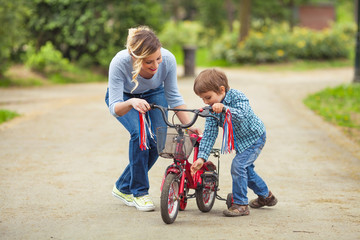 Cute little boy and his mother playing with bicycle in a park