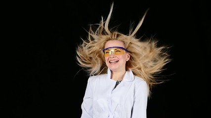 Young chemist blond hair dryer dries hair super on black. Slow