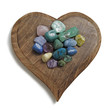 Multi colored crystal tumbled stones laid on wooden heart plaque