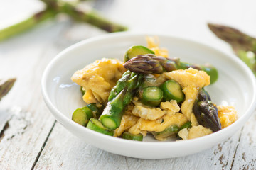 Green asparagus and eggs on wooden background