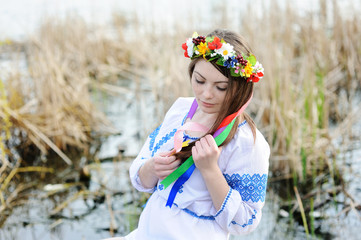 girl in the Ukrainian national shirt and floral wreath on her he