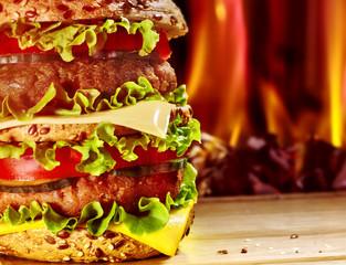 Hamburger with ham on wooden board .
