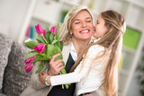 girl  giving flowers to his mom on mother