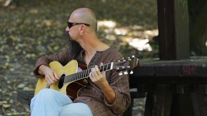 Musician practicing playing guitar outdoors