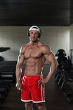 Aesthetic Man Listening Music In Modern Fitness Center poster