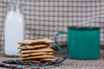 Stack of chocolate chip cookies with milk and cup of coffee