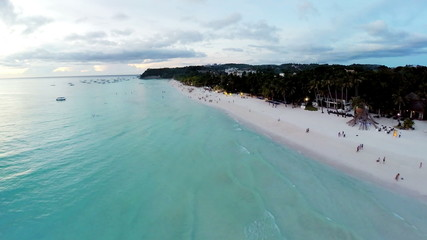 Aerial flight over sandy beach, waves and tourists