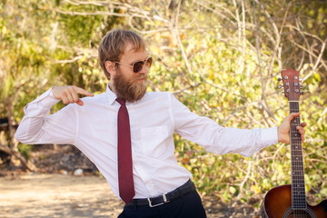 bearded guy in white shirt pose with guitar