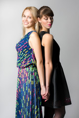 Two young sisters in fashion dresses staying back to back, one o