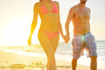 Summer beach couple romantic holding hands sunset