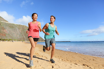 Runners running on beach - jogging couple